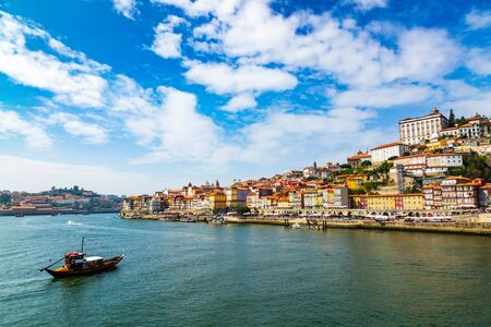 Porto, Portugal old town cityscape and the Douro River with traditional Rabelo boats