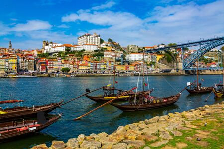 Porto, Portugal Riberia old town cityscape with Dom Lusi bridge and the Douro River with traditional Rabelo boats