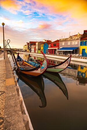 Aveiro, Portugal, Traditional colorful Moliceiro boats docked in the water canal among historical buildings. Banco de Imagens