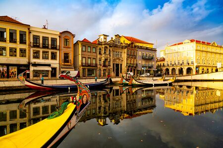Aveiro, Portugal, Traditional colorful Moliceiro boats in the water canal among historical buildings. Banco de Imagens