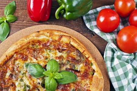 caloric: Italian homemade pizza with bacon on a wooden table