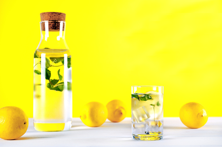 isotonic: Cold water with lemon and mint on yellow background