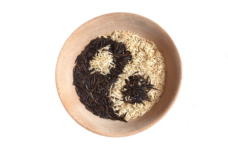 Yin and yang sign made of rice in wooden bowl.  photo