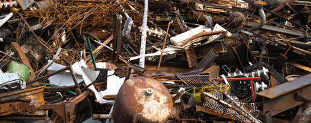 a pile of metal in a junkyard destined for recycling