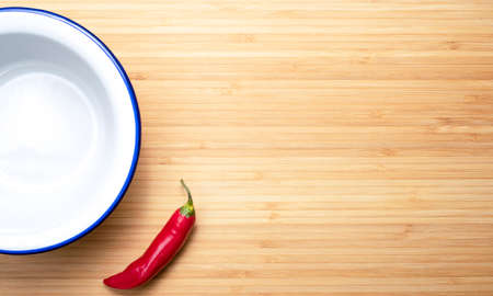 hot pepper and white plate on a wooden table