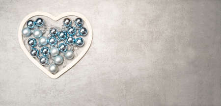 Christmas baubles arranged in a heart shape on a winter background