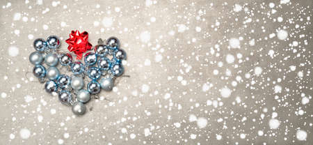 Christmas baubles in a gray and blue arranged in a heart shape on a winter background