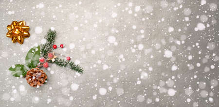 Christmas decoration and golden star on gray and winter background with falling snow