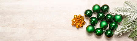Christmas decoration with a golden star and green baubles with a tree in the snow on the background