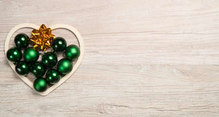 Christmas heart arranged with green baubles and golden bows on wooden background 免版税图像