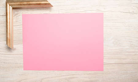 pink paper for text with golden frame and wooden background