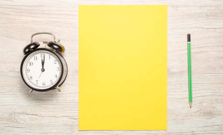 yellow blank card to write the text or resolutions for the new year with a clock and a pencil on a wooden background