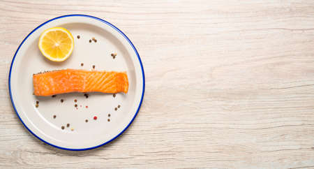 smoked salmon with lemon and colored pepper on a white plate and background with space for text 免版税图像