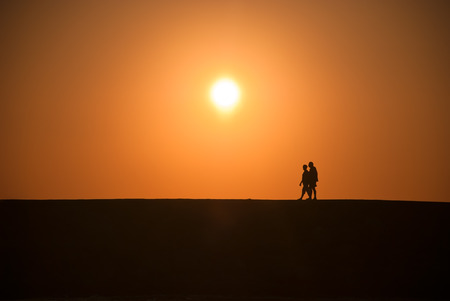 nostalgy: Two man walking during a sunset.