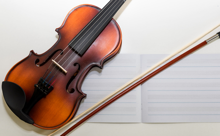 A Small Childrens Violin and Bow on a Childs Study Desk. Colorful letters  magnets in the background. A set-up for teaching children to play the violin. Stock Photo