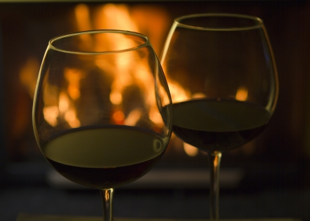 Two glasses of red wine with reflections from a nearby fireplace. Stock Photo - 16709046