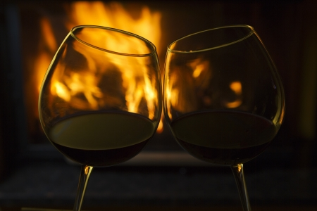 fireplace home: Two glasses of red wine with reflections from a nearby fireplace. Stock Photo