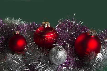 Red and silver Christmas baubles border on fur with a green background and copy space Stock Photo