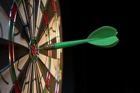shooting target: Green dart hitting the target.
