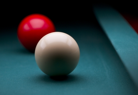 White and red carom balls with dark background