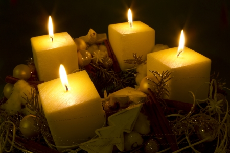 adventskranz: Beautifully decorated modern Christmas wreath with 4 lit candles.