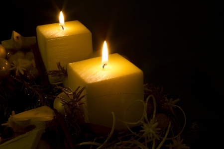 Two white candles with christmas decoration on black background with copy space.