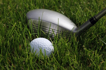 golf hybrid club with a golf ball lying in low rough Stock Photo - 16709049