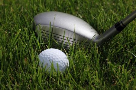 golf hybrid club with a golf ball lying in low rough