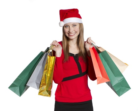 Beatiful young woman with Christmas hat holding several shopping bags