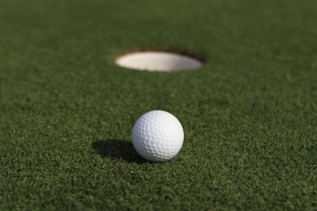 Golfball close to hole Stock Photo