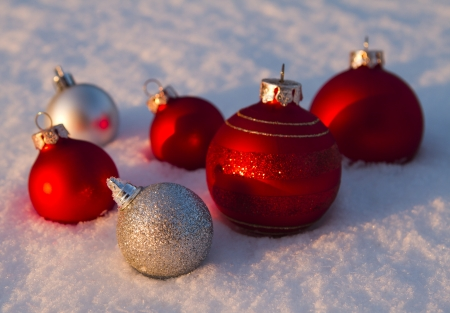 Red and silver Christmas baubles in snow