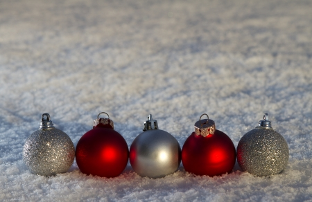 Red and silver Christmas baubles on snow