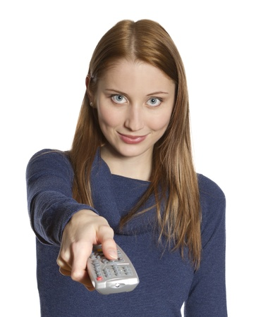 Attractive young woman points remote control at viewer  focus on face