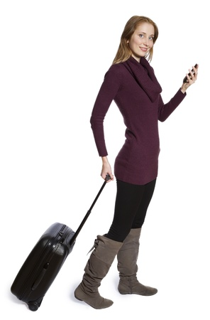 Attractive young women holding mobile phone travelling with suitcase against white background