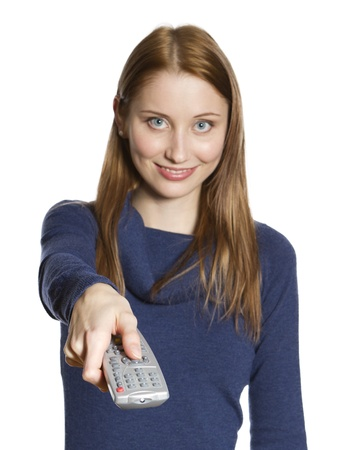Attractive young woman points remote control at viewer (focus on remote control)
