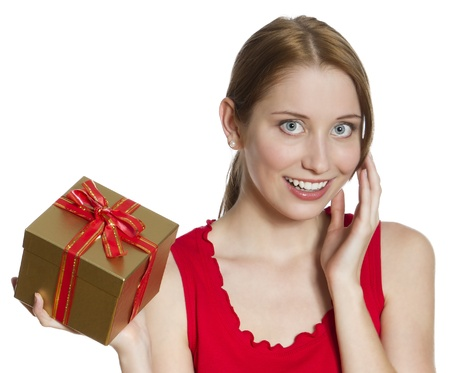 Young woman in a bright red dress, holding a golden gift box with a surprised delighted expression on her face; isolated on white