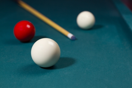 pool hall: White and red carom balls with billiard cue on pocketless table Stock Photo