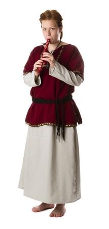 flauta: Niña descalza medieval tocando la flauta, aislado en blanco