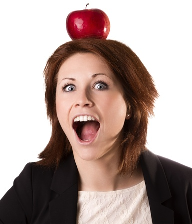 Young surprised businesswoman balancing an apple over head, isolated on white photo