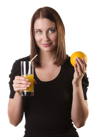 Close up of a healthy young woman holding orange and drinking fresh juice with a straw