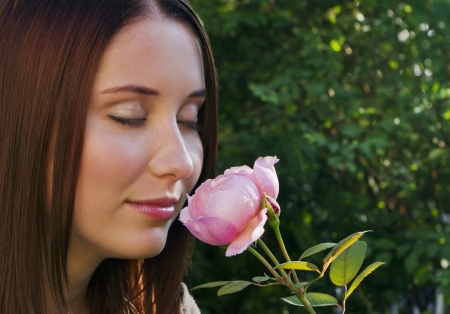 Closeup of beautiful young brunette girl smelling roses Stock Photo