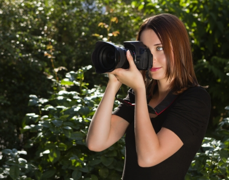 Beautiful young smiling girl making photo with digital SLR camera photo