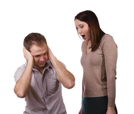 Man shutting his ears and not listening to the persistent yelling of his spouse photo