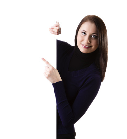 Woman showing and pointing at blank billboard sign banner, young smiling brunette, isolated on white background