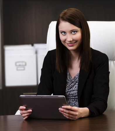 Beautiful young business woman using tablet PC in the office