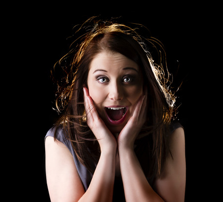 Shocked woman portrait isolated on black background with backlight