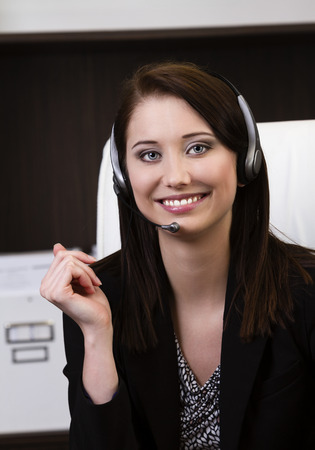 Close up of happy female help desk operator working in a modern office