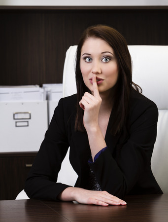 Portrait of attractive young business woman gesturing keep silence sign in a modern office