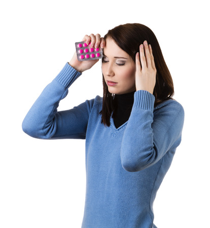 A young attractive woman with pills in her hand suffering from illness or headache holding her head, isolated on white