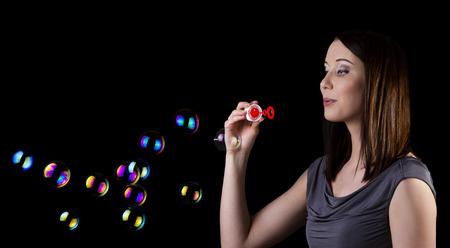 Attractive young brunette blowing bubbles, isolated on black